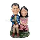 The couple sit on a stone custom bobbleheads