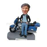 Custom bobbleheads stands behind the motobike
